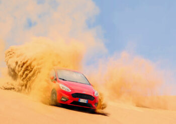 Red Ford Fiesta racing on dusty road