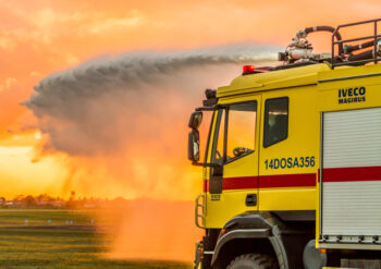 Yellow fire engine shooting very large water jet