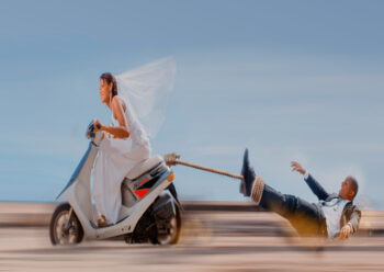 Bride on scooter with groom in tow