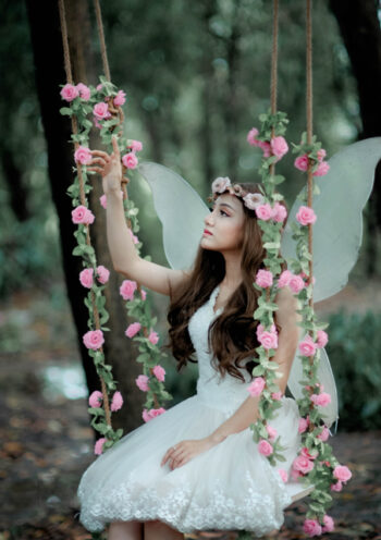 Female dressed as an angel sitting on a floral swing