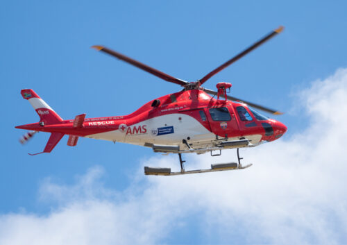 Red and white helicopter in flight
