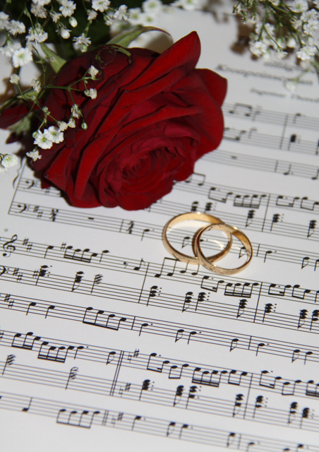 Two gold wedding rings laying on music next to a red rose