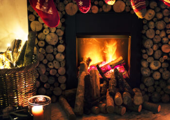 Fire with logs around the chimney and Christmas stockings hung above the fire