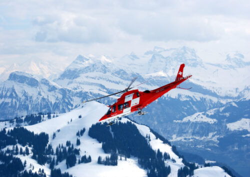 Red and white helicopter flying near snow covered mountains