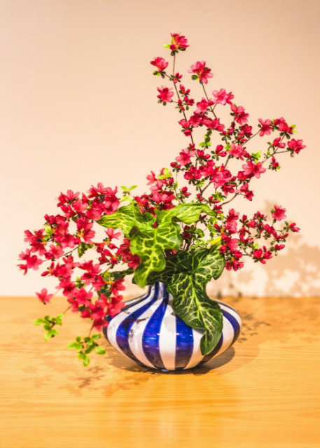 Red flowers in blue and white striped vase