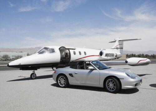 Convertible silver Porsche parked by private jet birthday card